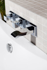 Close up view of mixing faucet in tiled bathroom