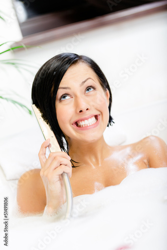 Woman lying in bathtub with suds plays with shower head