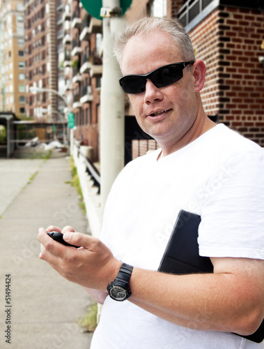 Man on city street with cell phone