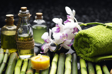Spa setting green towel and massage oil ,candles