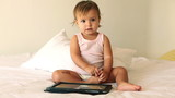 Adorable little girl playing with digital tablet on bed