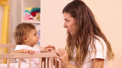 Beautiful mother speaking story to girl which standing on bed