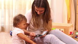 Education: mother reading book to small girl at home