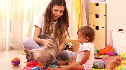 Beautiful mother and girl  playing with cat at home