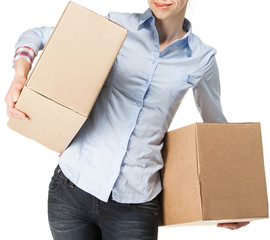 Smiling woman carrying two big boxes, isolated on white