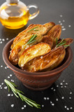 Baked potatoes with rosemary and salt in a rustic bowl
