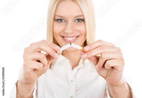 Young woman breaking a cigarette isolated on white