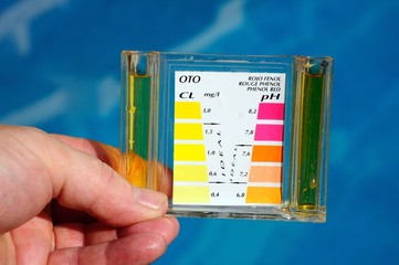 Holding a pool analysis kit  by pool © Arena Photo UK