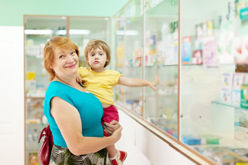 woman with child chooses  at  pharmacy