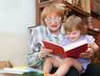 Mature woman and baby girl reads book