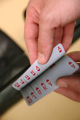 Human hand showing playing cards on the glass table