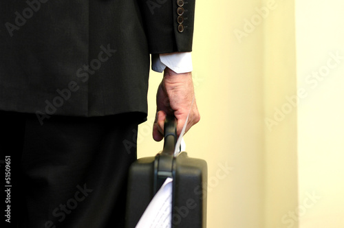 Businessman holding overloaded briefcase