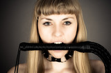 submissive woman holding a whip in his mouth
