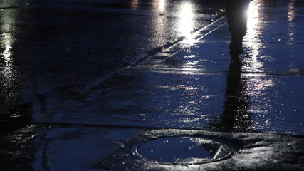 Woman walks by on rainy night.