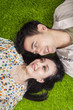 Happy couple lying on grass in the park