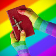 Old hands holding a very old bible, rainbow flag pattern