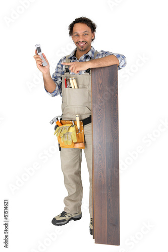 Man standing by laminate flooring with a mobile telephone