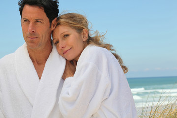 Couple stood on beach wearing bath gowns