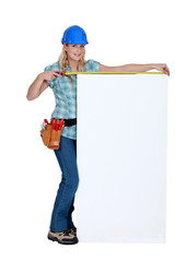 Tradeswoman measuring a blank sign