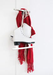Lady skates and red scarf hanging on the door