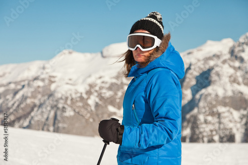 Ski woman with goggles in snow mountain landscape with blue sky.