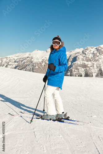 Ski woman in snow mountain landscape with blue sky.