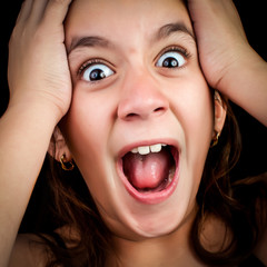 Girl screaming loudly on a black background