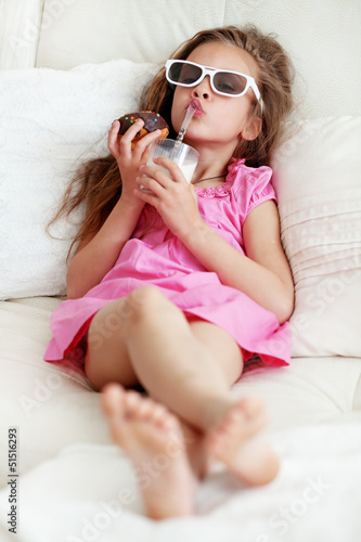 Kid girl eating on a sofa