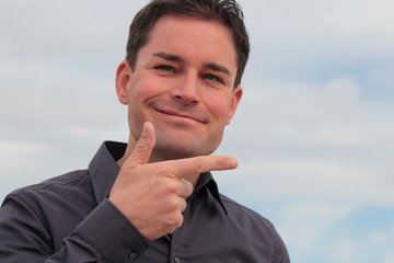 Attractive man pointing with his right hand
