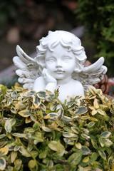 Engelfigur schaut über Hecke