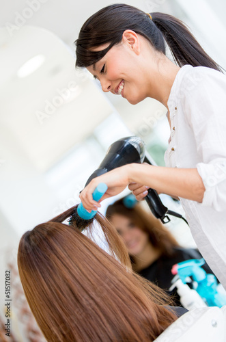 Hairdresser blowing woman's hair
