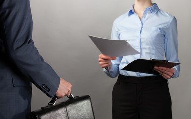Businesswoman reaches out documents to a businessman with briefc