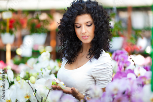 Woman looking for flowers in a greenhouse