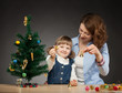 Happy smiling baby girl and her mummy decorates the Christmas tr