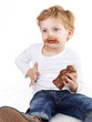 Cute little boy eating chocolate