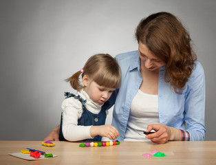 Young mother and her dauther modelling with plasticine