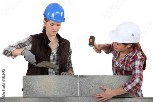A team of tradeswomen laying cinder blocks