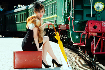 Retro girl sitting on suitcase at the train station