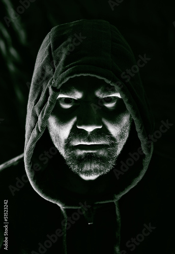 Scary evil man with hood in darkness