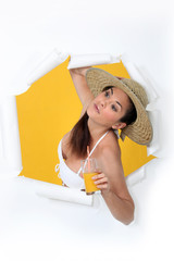 Woman with orange juice bursting out of a paper screen