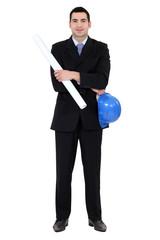 Businessman holding helmet and blueprints