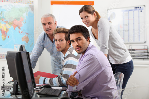 Group of casually dressed people working round a computer