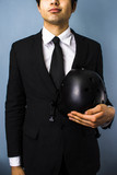 Businessman holding helmet