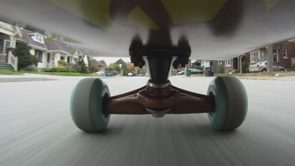 Riding a skateboard down a suburban Toronto street..