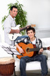 Father teaching son how to play the guitar