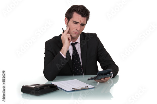 Confused man holding calculator
