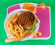 Hamburger, french fries on plate on scale on green background