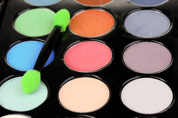 Bright eye shadows and sponge brush for foundation close up