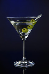 Martini glass with olives on dark blue background