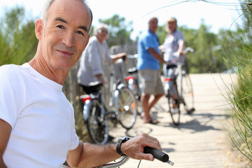 a senior man doing bike with friends in summer
